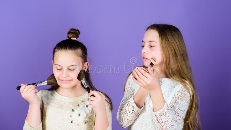Fabrication pour peler la lueur avec le maquillage Peu maquilleurs Petites filles appliquant le maquillage sur la peau de visage  image stock