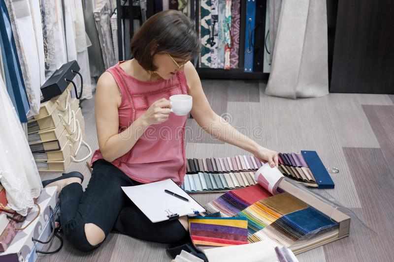 Fabrics Store, adult female looking and touching samples, female designer chooses fabrics for interior decoration stock photography
