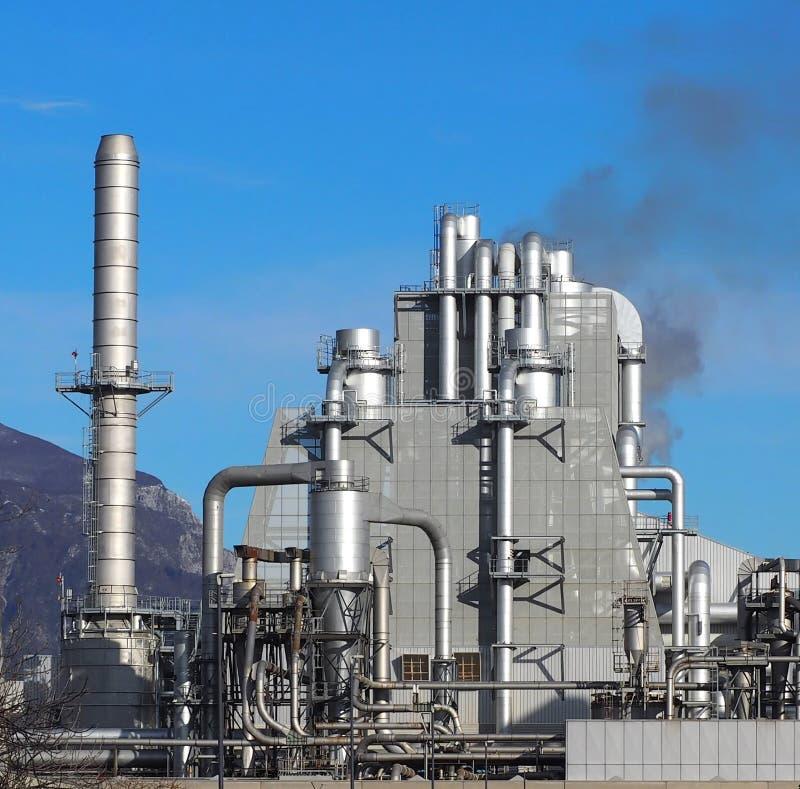 Fabriek met een lange metaalschoorsteen en vele pijpen rond een industrieel gebouw stock foto's