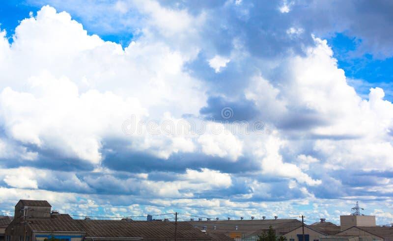 Fabriek onder de grote wolken en de blauwe hemel stock afbeeldingen