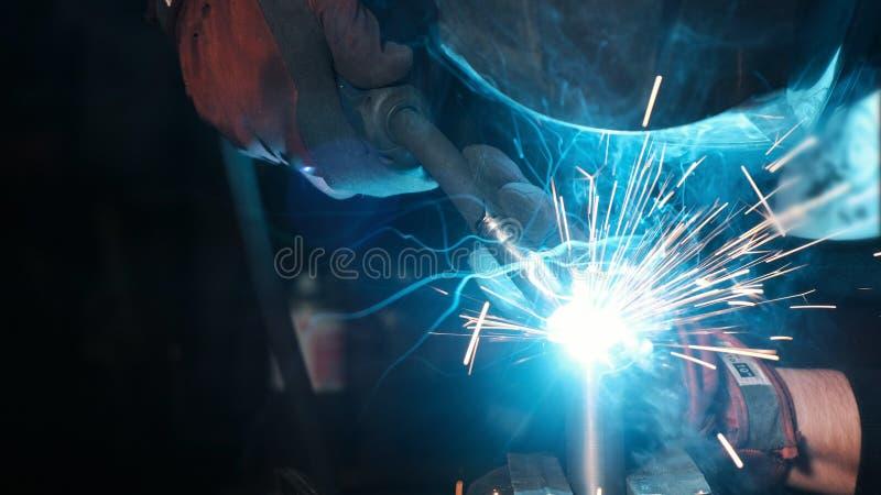 Fabrieksarbeider in beschermend masker dat moderne lassenmachine om metaalbouw met behulp van bij de productie te lassen stock afbeelding