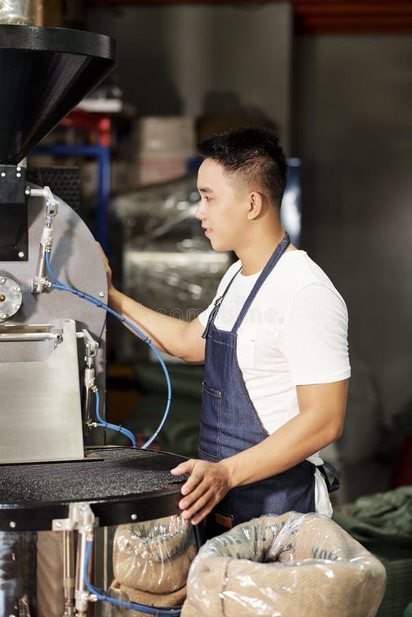Fabrieksarbeider die aan koffiemachine werken stock afbeelding