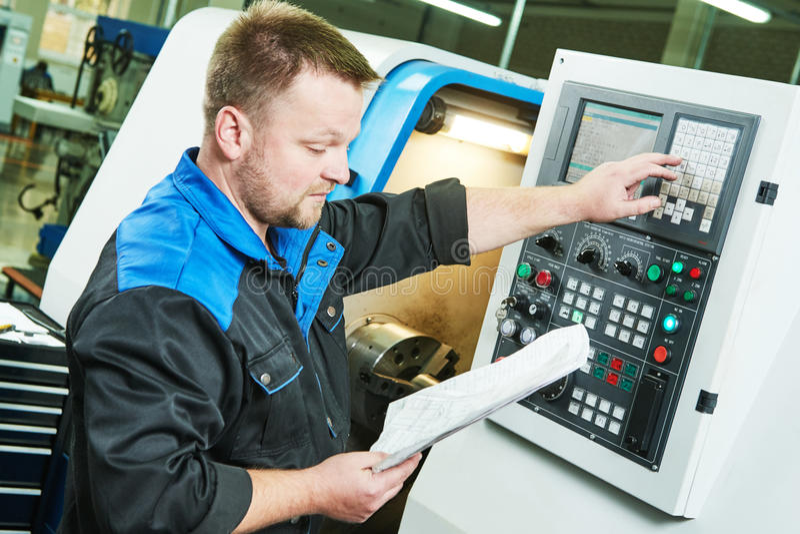 Fabrieksarbeider die cnc het draaien machine in metaal in werking stellen die de industrie machinaal bewerken stock fotografie