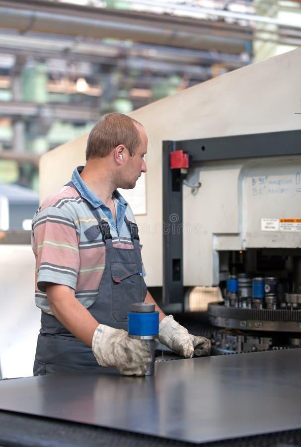 Fabrieksarbeider die gecoördineerde ponsenmachine in werking stellen royalty-vrije stock afbeeldingen