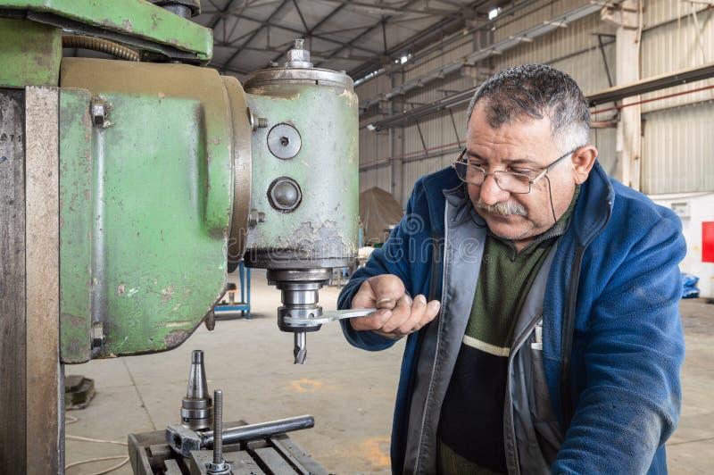 Fabrieksarbeider die malenmachine in workshop met behulp van stock foto