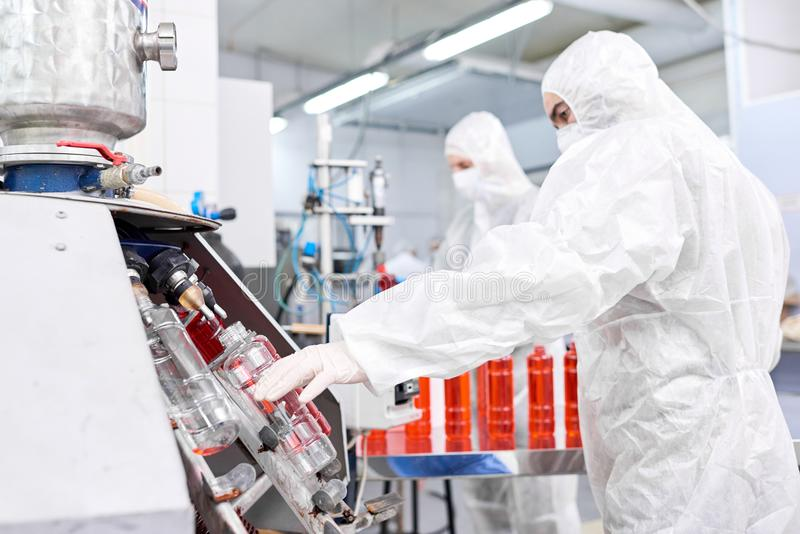 Fabrieksarbeider die plastic fles zetten in het vullen machine stock afbeelding