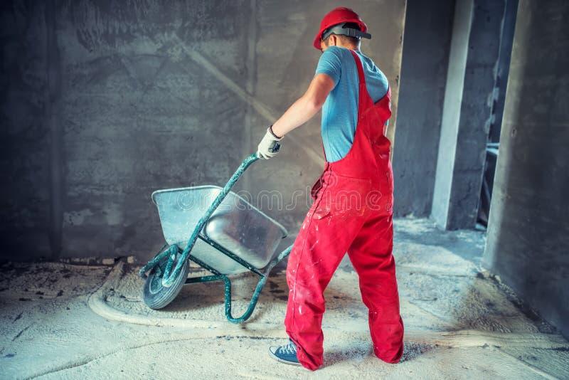 Fabrieksarbeider, ingenieur op bouwwerf, die een kruiwagen duwen stock fotografie