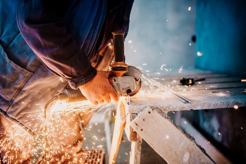 Fabrieksarbeidershanden die ijzer met hoekmolen snijden De details van de fabrieksproductie stock foto's
