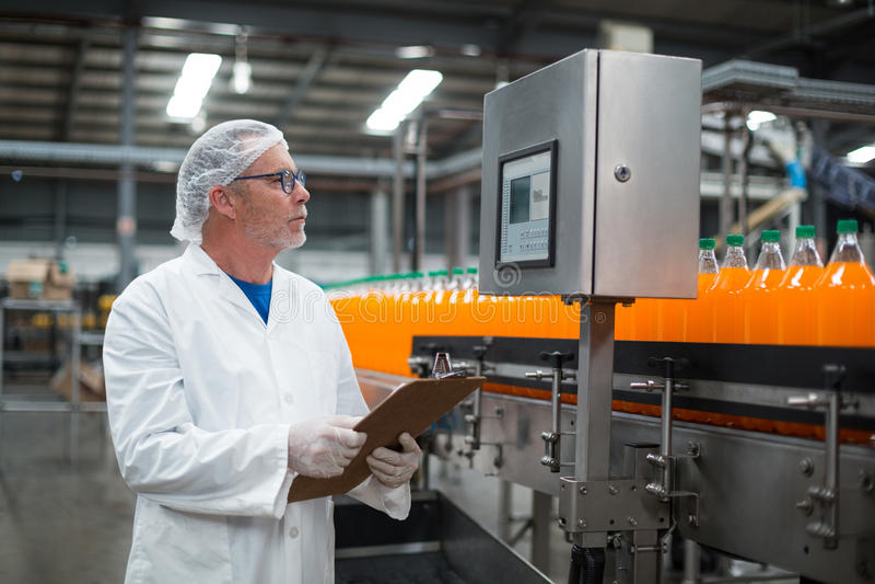 Fabrieksingenieur die verslag op klembord in fabriek handhaven stock fotografie