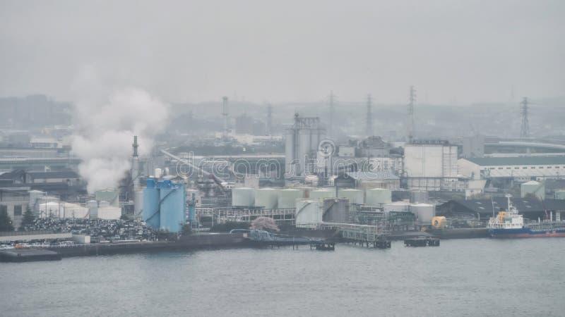 fabriekspijpen met rook dichtbij haven stock afbeelding