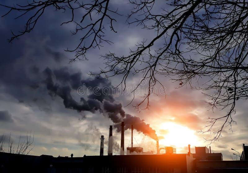 Fabrieksschoorstenen met zwarte rook Fabrieksschoorstenen Blauwe achtergrond Het concept van de milieuverontreiniging Ecologisch  stock afbeelding