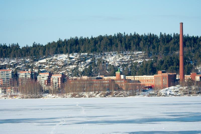 Fabrik durch gefrorenen See lizenzfreie stockfotografie