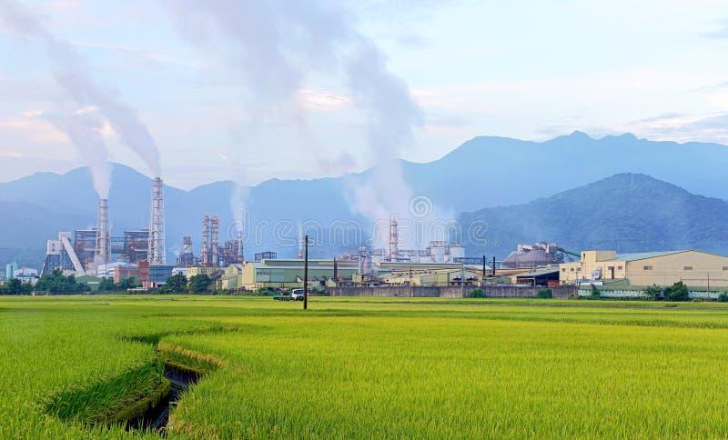 Fabrik i mitt av en grön jordbruksmark på en molnig dag arkivfoto
