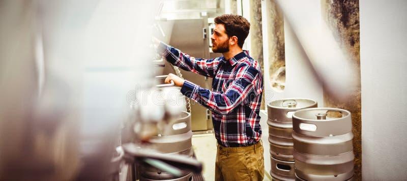 Fabrikant het inspecteren mechanisme in brouwerij stock afbeeldingen