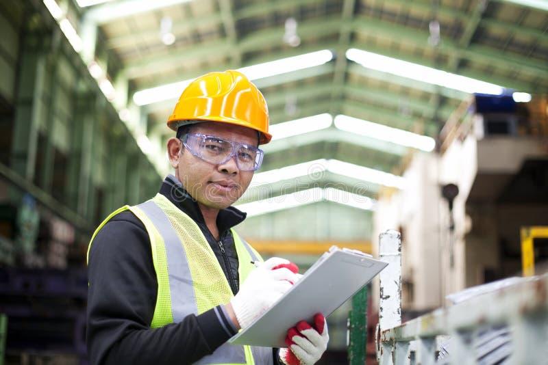 Fabriksarbetare med skrivplattan på handen arkivfoton