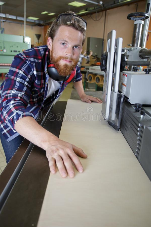 Fabriksarbetaren fungerar laser-klippmaskinen i seminarium arkivbilder