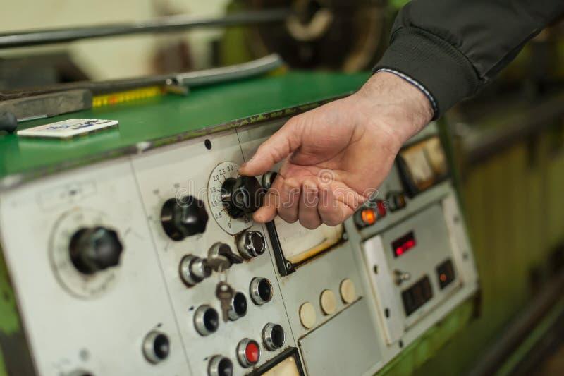 Fabriksarbetaren justerar kontrollbordet av branschmaskinen royaltyfri fotografi