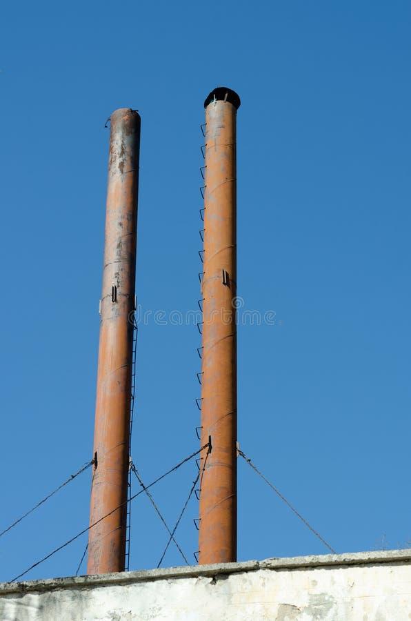 Fabrikschornsteinspitzen gegen blauen Himmel lizenzfreies stockfoto