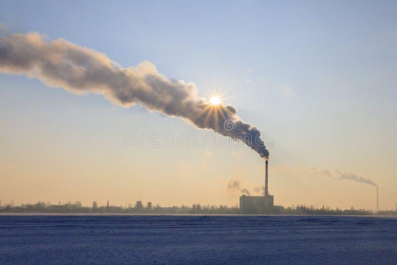 Fabriksrör nära sjön och röken som stänger solen royaltyfria bilder