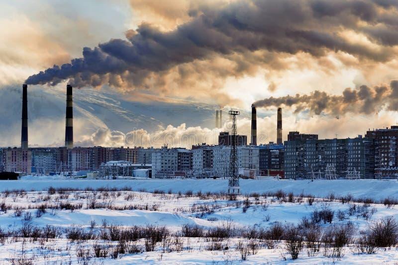 Fabriksskorsten som förorenar luften över staden royaltyfri fotografi