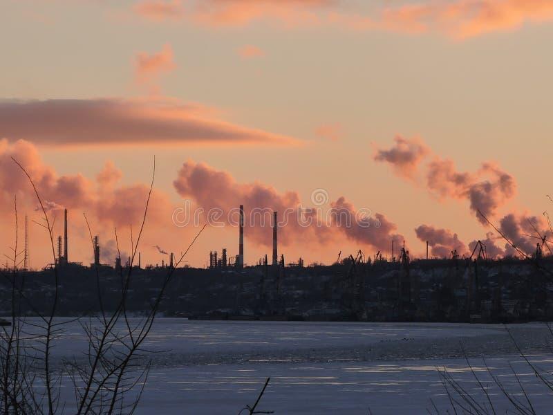 Fabriksskorstenfabrik med svart rök över himlen med molnet när solnedgångtid, bransch och föroreningbegrepp arkivbild