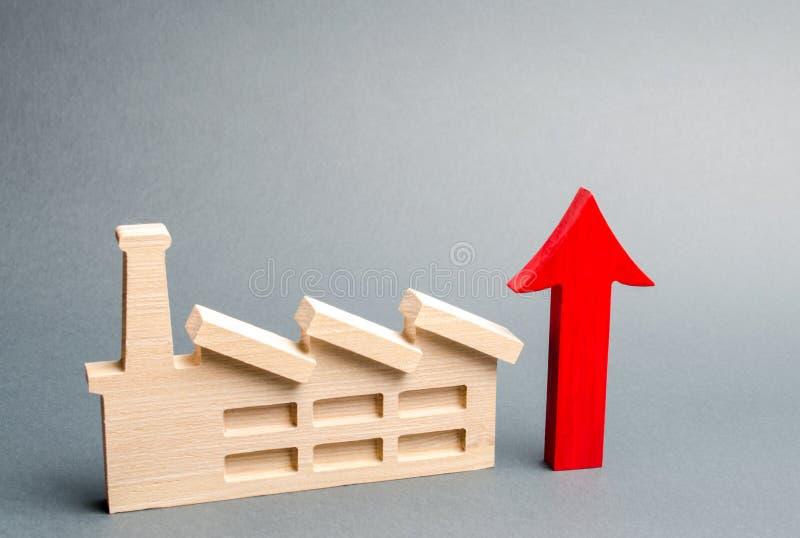 Fabriksstatyett och röd övre pil Begreppet av tillväxt i nivån av produktion och utvecklingen av bransch ekonomiskt arkivfoto