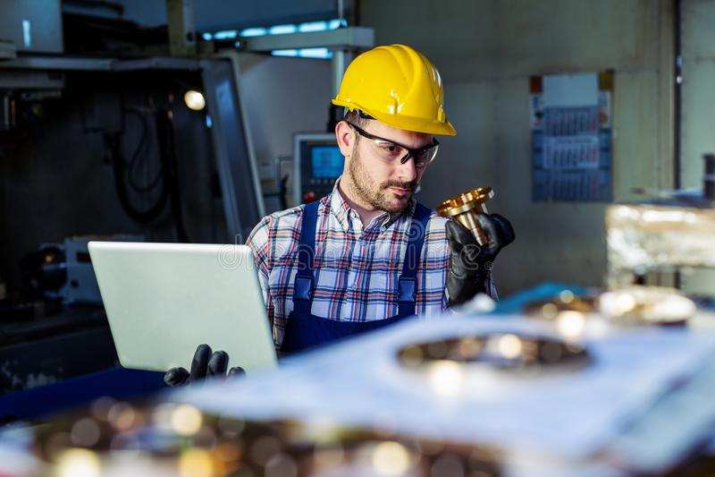 Fabriksteknikern kontrollerar kvaliteten av den tillverkade delen royaltyfri fotografi