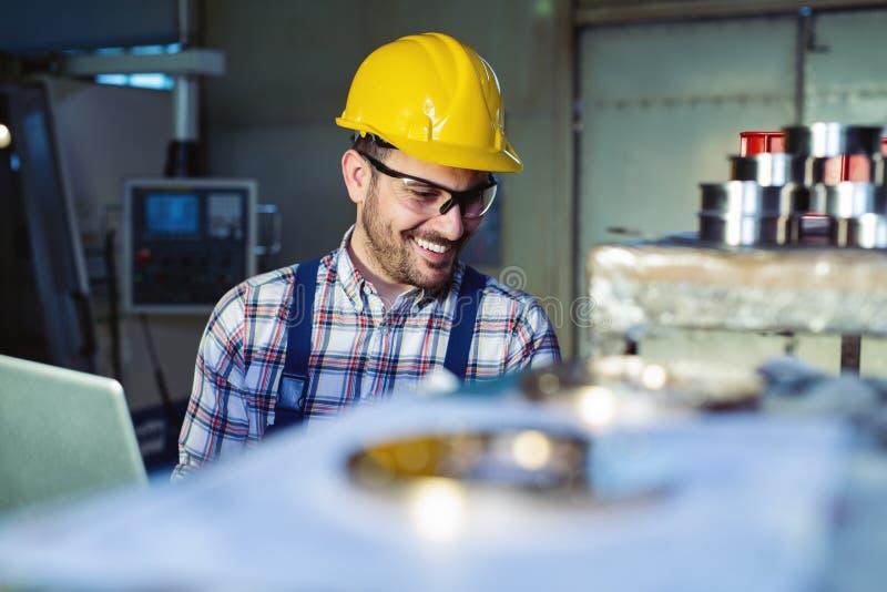 Fabriksteknikern kontrollerar kvaliteten av den tillverkade delen royaltyfri foto