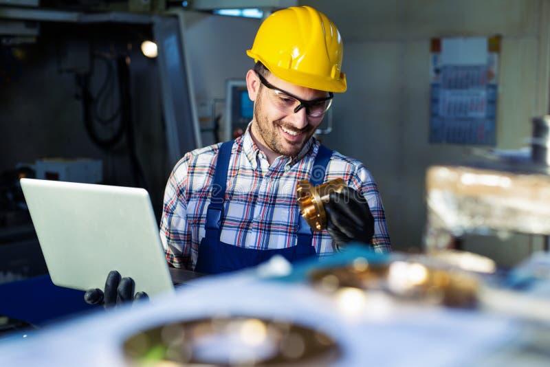Fabriksteknikern kontrollerar kvaliteten av den tillverkade delen royaltyfri bild