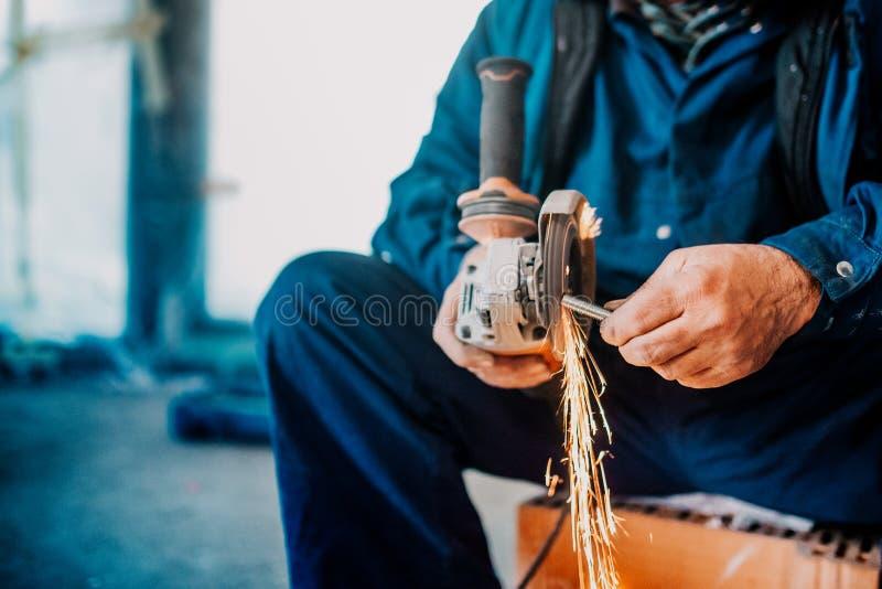 Fabryczny przemysłowego pracownika rozcięcia żelazo i metal używać ostrzarza i wytwarzający iskry na budowie obrazy royalty free