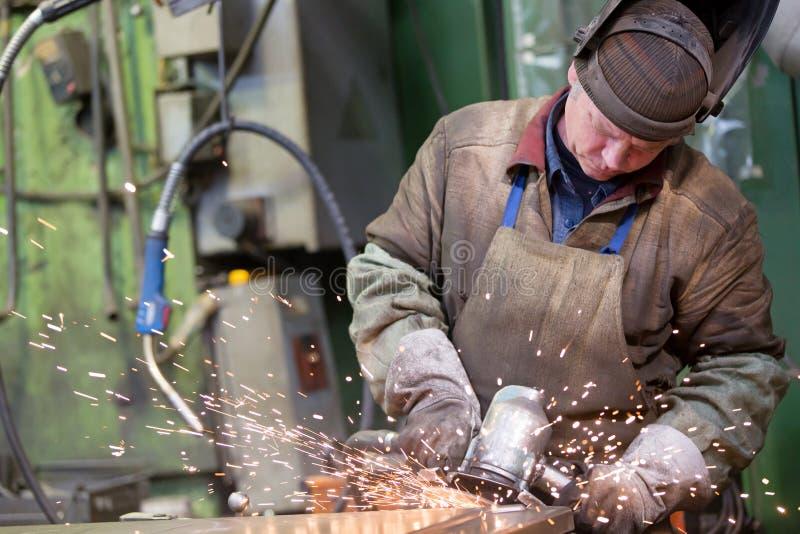 Fabryczny spawacza pracownik mleje stalowego prześcieradło zdjęcie stock