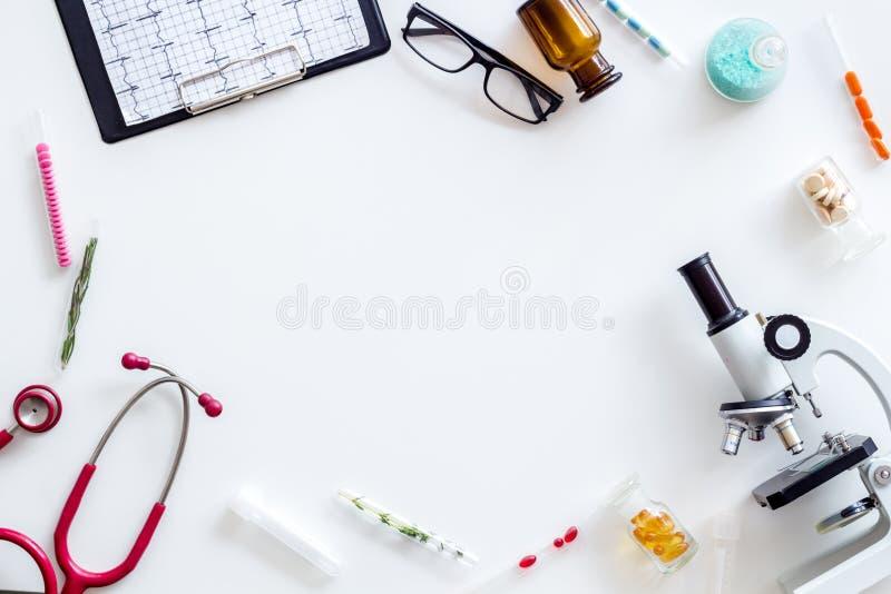 Fabrykuje biurko w laboratorium z mikroskopem, stetoskop, kardiogram rama dla badawczego białego tło odgórnego widoku egzaminu pr obraz royalty free