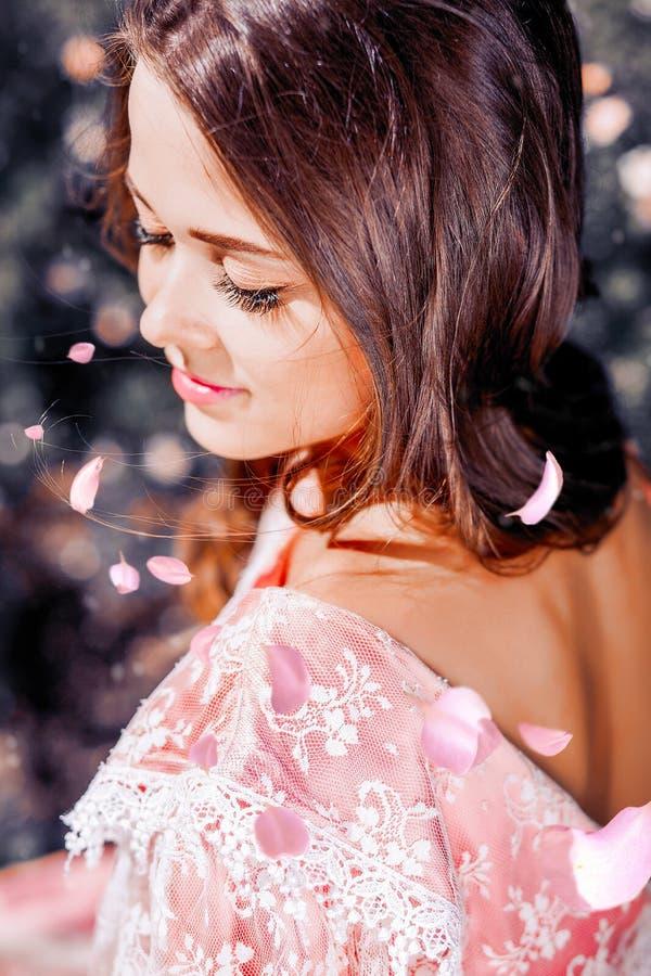 Fabuloso y chica joven con el pelo hermoso en un vestido del rosa del vintage en el jardín foto de archivo