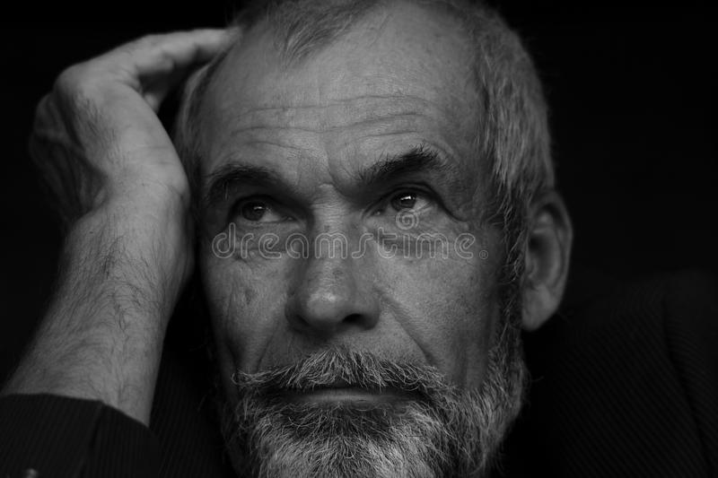 Fabulous at any age concept. Close up portrait of handsome mature man with beard and moustache. Monochrome indoor shot royalty free stock photo