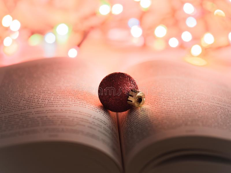 Red glitter Christmas ornament on an open book with Christmas lights in the background stock images