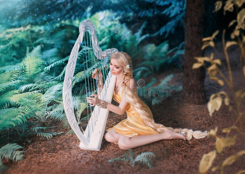 Fabulous forest elf sits under tree and plays on white harp, girl with long blond hair braided in long yellow dress. Summer goddess rests and sings to the royalty free stock photography