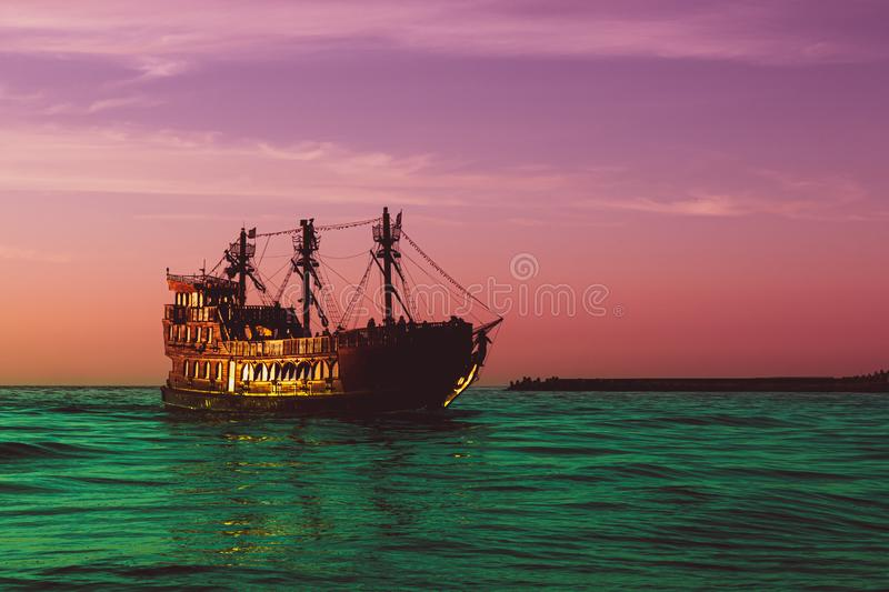 A fabulous golden vintage ship sailing on a surreal green sea against a purple - red sky, concept of fairy tales and magic royalty free stock image