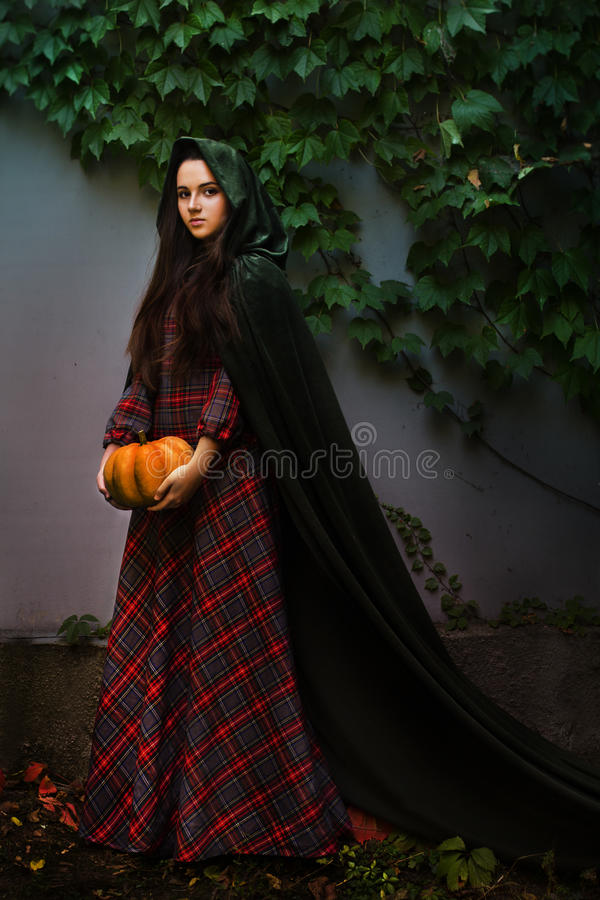 Fabulous Medieval girl in plaid dress with pumpkin. Fabulous Medieval girl in plaid dress in a green hooded cloak with pumpkin on a background of ivy royalty free stock image