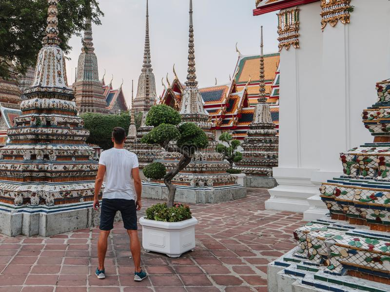 Fabulous, mystical, Buddhist Asian temple. Tourist on vacation. A man walks around the ancient pagodas. Wat Pho in royalty free stock photography