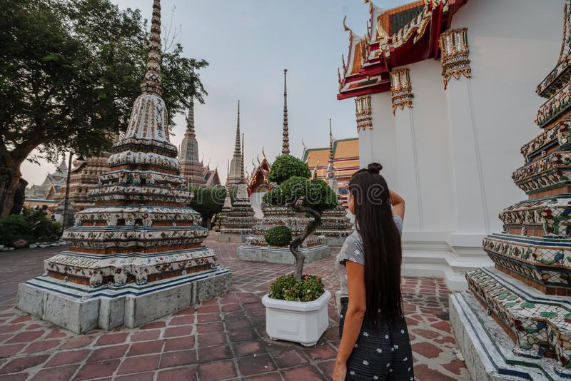 Fabulous, mystical, Buddhist Asian temple. Woman impressed with the beauty of the place. Tourist girl walks through the stock images