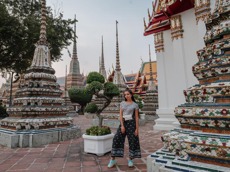 Fabulous, mystical, Buddhist Asian temple. Woman impressed with the beauty of the place. Tourist girl walks through the stock photo