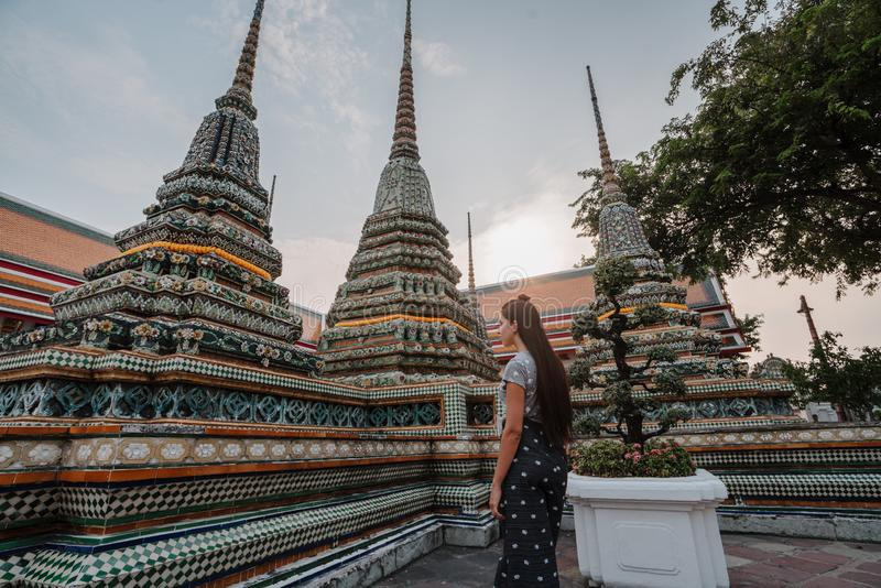 Fabulous, mystical, Buddhist Asian temple. Woman impressed with the beauty of the place. Tourist girl walks through the royalty free stock image