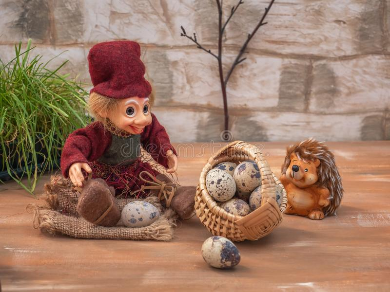 Fabulous picture with small toys. Hedgehog and Lesovik rest in the forest. They carry a large basket of quail eggs. Fabulous picture with small toys. Hedgehog stock image