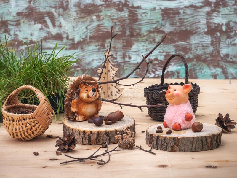 A fabulous picture with small toys, a Hedgehog and a pink pig are resting on stumps, tired of harvesting nuts in the forest stock images