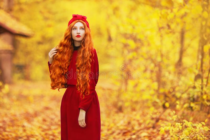 Fabulous redhead woman with long curly hair in red dress on blurred autumn background. Girl on fabulous background of forest with royalty free stock images