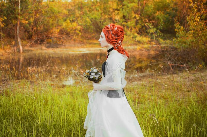 Fabulous renaissance princess in white dress with hairstyle on nature background. Rococo queen in white wedding dress. Fabulous royalty free stock photos