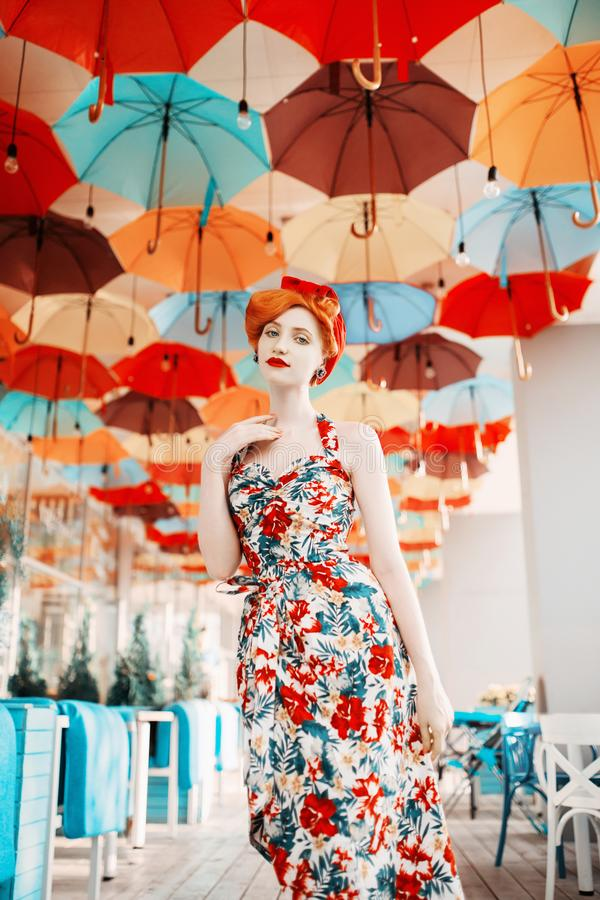 Fabulous retro girl with hairstyle in flower dress on background of colored umbrellas. A beautiful vintage woman with pale skin. And red lips. Stylish lady stay stock photography