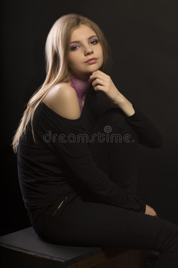 Fabulous young woman with glitter on her neck posing at the dark stock photos