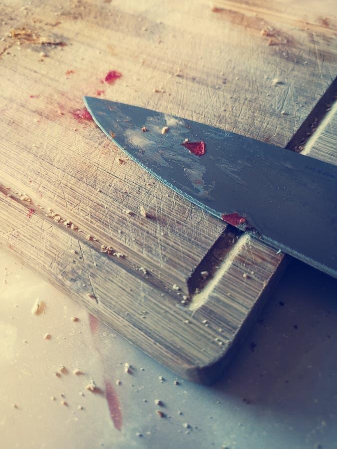 Faca da lâmina que encontra-se em uma placa de madeira suja faca manchada com corte de ingredientes para o jantar fotos de stock royalty free