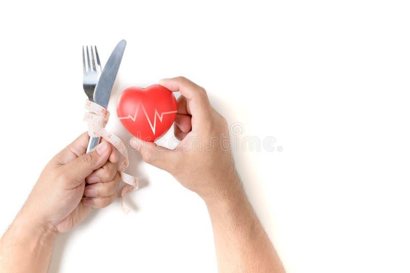 A faca da terra arrendada do homem da mão envolveu a fita e o coração vermelho fotos de stock